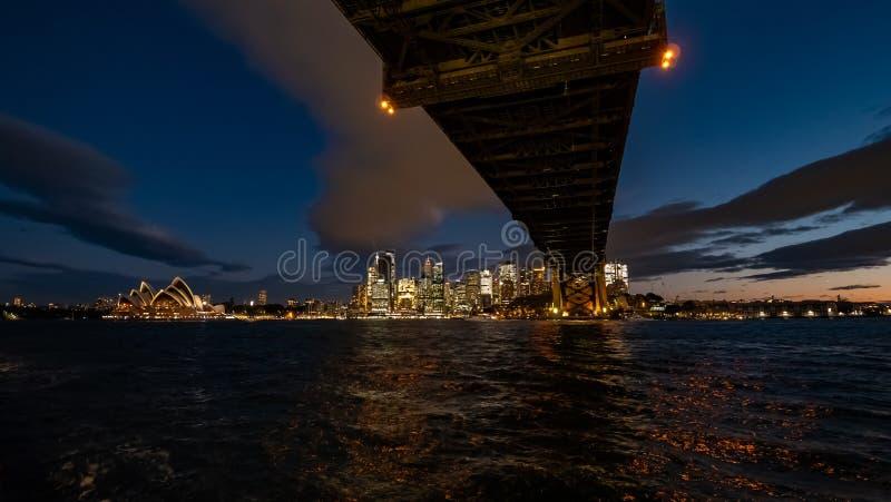 Visión de debajo el puente del puerto hacia Sydney en la noche imagenes de archivo