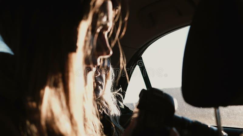 Visión dentro del coche La mujer turística que viaja en coche y que toma las fotos de la puesta del sol ajardina fuera de la vent fotos de archivo libres de regalías