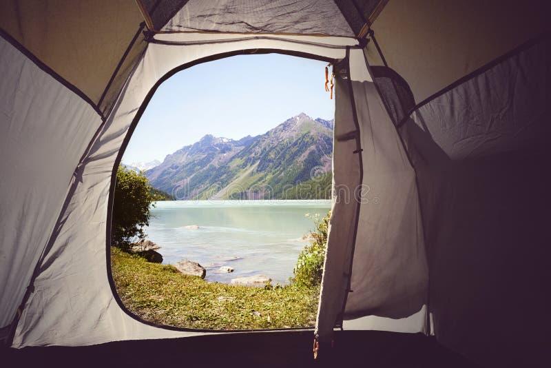Visión desde adentro fuera de la opinión amarilla del lago del tentA El acampar en las maderas Lago Kucherlinskoe mountain desde  imagen de archivo