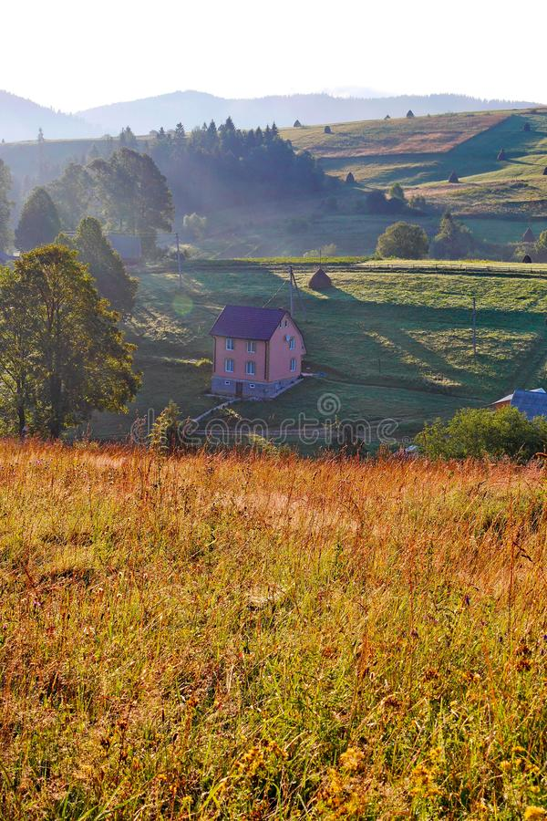 Visión desde arriba de la colina a un valle iluminado por el sol con una casa de dos pisos, los campos y los árboles contra un ci foto de archivo libre de regalías