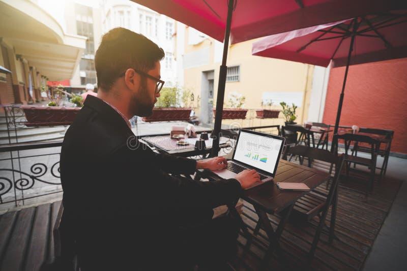Visión desde del hombre de negocios con el ordenador portátil en barra de la calle imagen de archivo