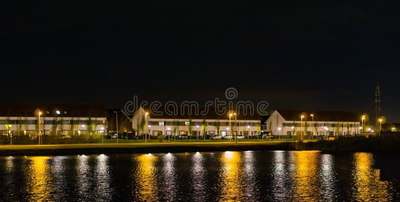 Visión desde el agua en casas y el camino de la conducción en la noche, opinión holandesa de la calle de landschapsbaan, el Meern foto de archivo