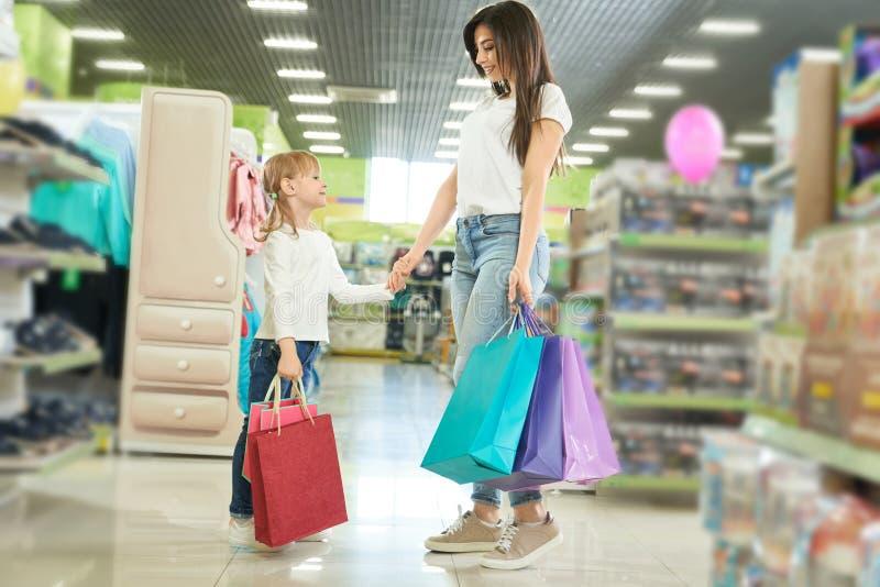 Visión desde el lado de la familia feliz que compra nuevos juguetes en tienda imagen de archivo