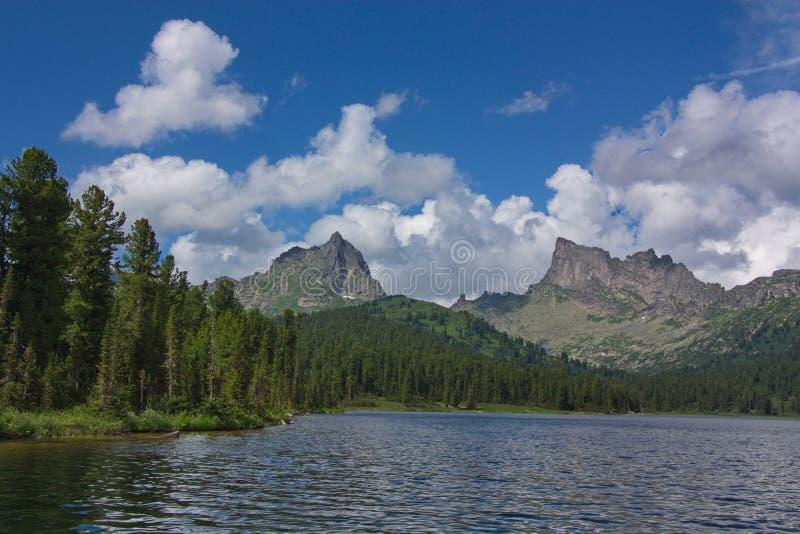 Visión desde el lago en picos de montaña fotografía de archivo