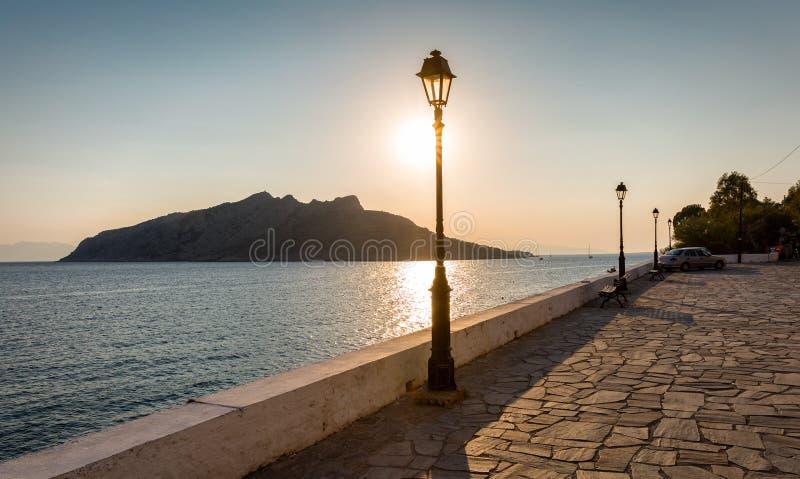 Visión desde el pueblo de Perdika, isla de Aegina a Moni Island durante puesta del sol fotos de archivo