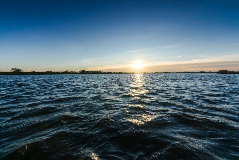 Visión desde el punto bajo sobre el agua de ondulación de un río imagenes de archivo