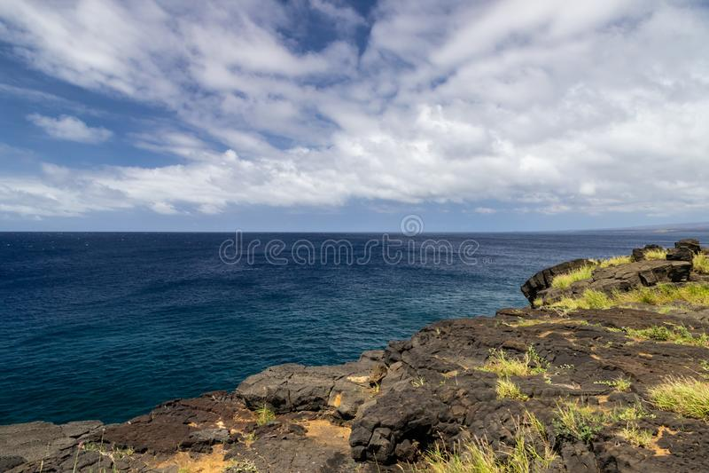 Visión desde el punto del sur en la isla grande de Hawaii Roca de la lava en primero plano; Océano Pacífico, cielo azul y nubes e fotos de archivo libres de regalías