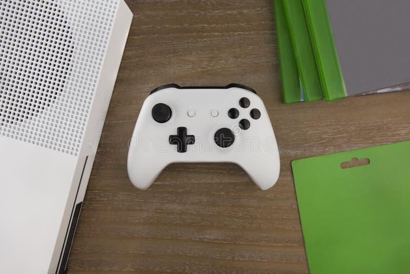 Visión desde el top en el cojín del juego, la videoconsola y discos del juego imagen de archivo