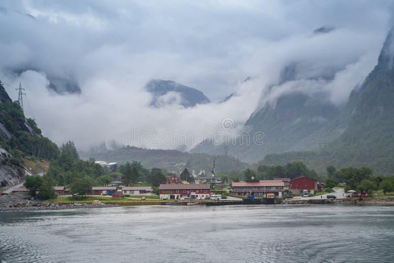 Visión desde el transbordador de Lysefjord a la ciudad de Lusebotn debajo de las montañas foto de archivo libre de regalías