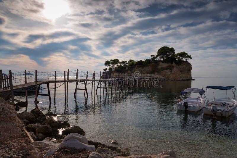 Visión desde la isla de Agios Sostis y del camafeo Una pequeña isla hermosa con el puente de madera y la turquesa riegan Zakyntho foto de archivo