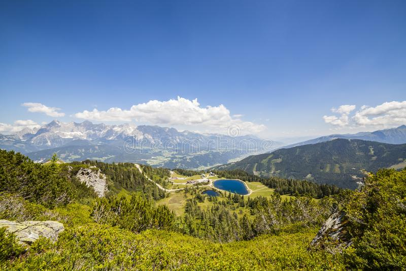 Visión desde la montaña Gasselhoehe al lago y la montaña distante Dach imagen de archivo