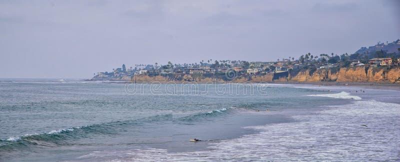 Visión desde la playa de la misión en San Diego, de los embarcaderos, embarcadero y arena, alrededor de personas que practica sur imágenes de archivo libres de regalías