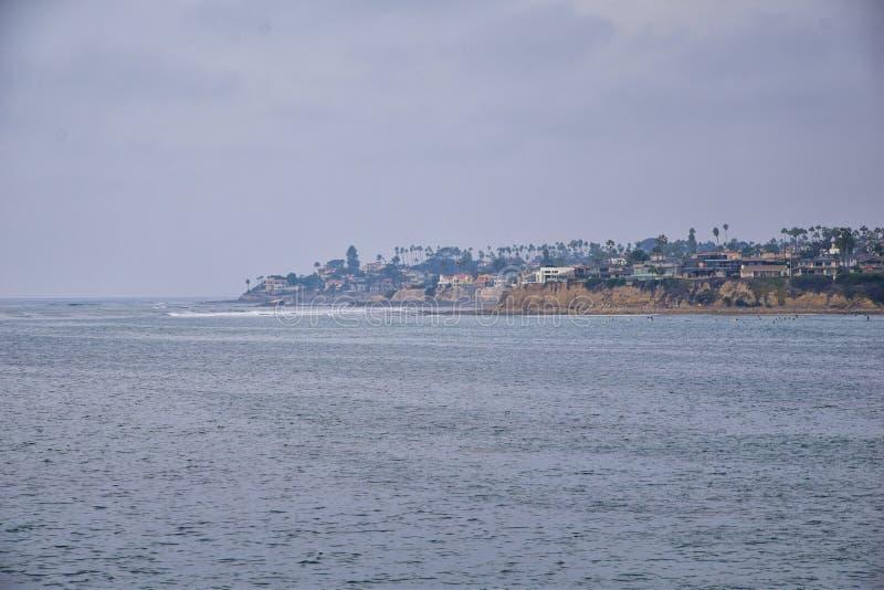 Visión desde la playa de la misión en San Diego, de los embarcaderos, embarcadero y arena, alrededor de personas que practica sur fotografía de archivo