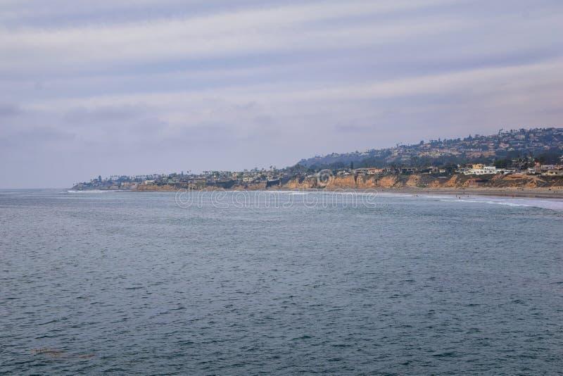 Visión desde la playa de la misión en San Diego, de los embarcaderos, embarcadero y arena, alrededor de personas que practica sur imagen de archivo