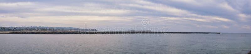 Visión desde la playa de la misión en San Diego, de los embarcaderos, embarcadero y arena, alrededor de personas que practica sur imagen de archivo libre de regalías