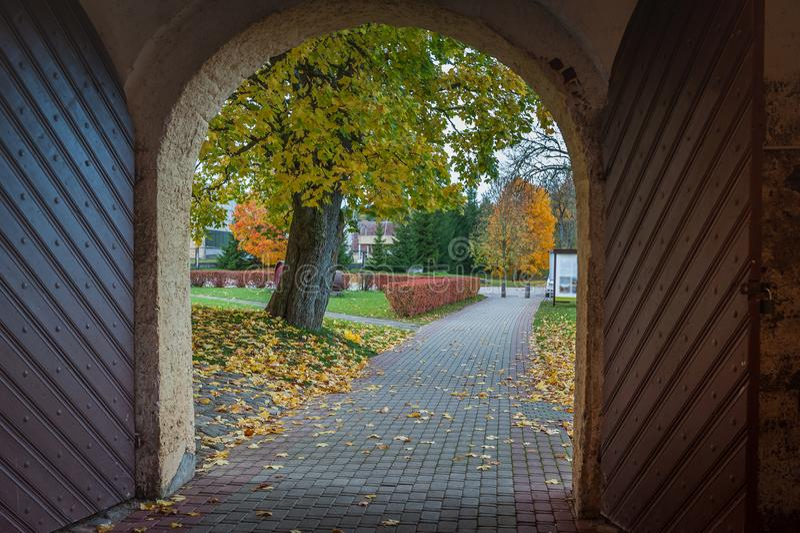 Visión desde la puerta de madera arqueada abierta al paisaje del otoño Señorío de Slokenbeka fotos de archivo