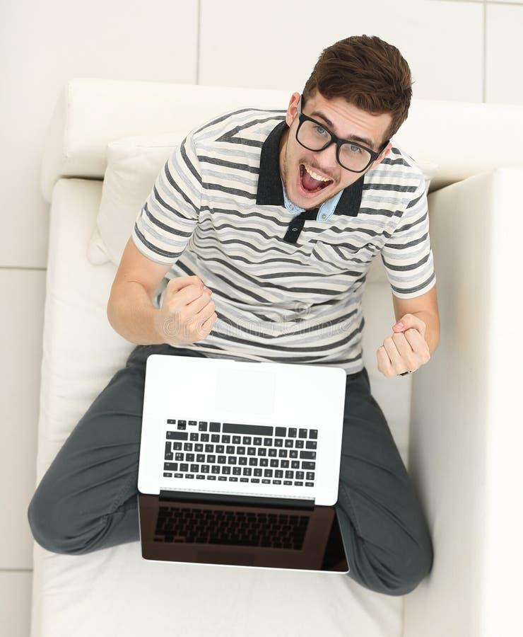 Visión desde la tapa hombre joven jubiloso con el ordenador portátil que se sienta en el sofá fotografía de archivo