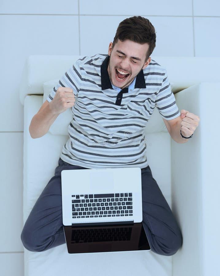 Visión desde la tapa hombre joven jubiloso con el ordenador portátil que se sienta en el sofá foto de archivo libre de regalías
