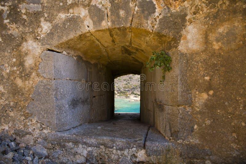 Visión desde la ventana de la fortaleza de Spinalonga al mar azul imagenes de archivo