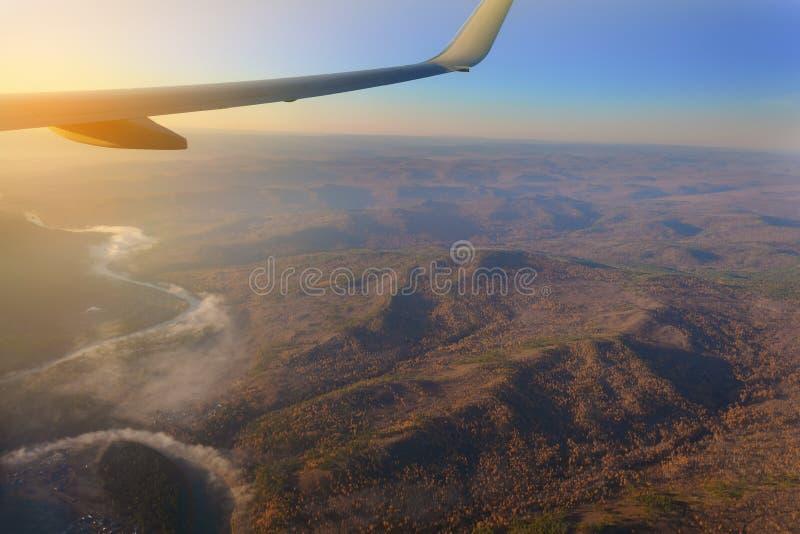 visión desde la ventana del avión al horizonte del lago y del río en las montañas con los bosques en la puesta del sol del día imagen de archivo