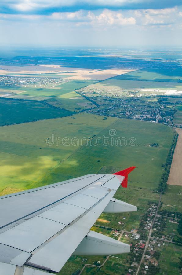 Visión desde la ventana del avión a las ciudades y a los campos foto de archivo