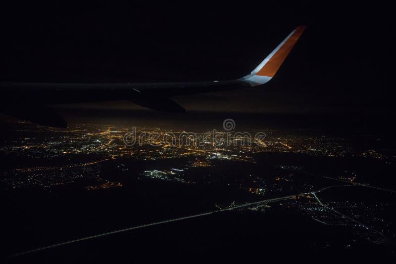 Visión desde un aeroplano de aterrizaje hacia fuera la ventana de la ciudad Luces brillantes fotos de archivo libres de regalías