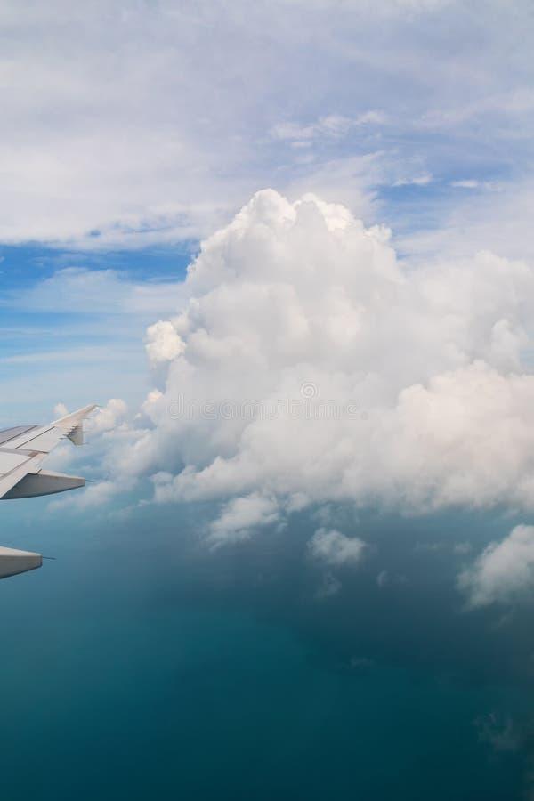 Visión desde un aeroplano en el ala de un aeroplano y de las nubes de cúmulo sobre el mar imagenes de archivo