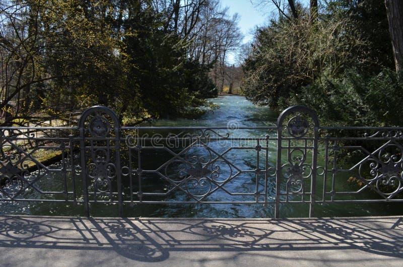 Visión desde un puente con la barandilla agradable hecha a mano y el río que fluye y árboles en el fondo fotografía de archivo