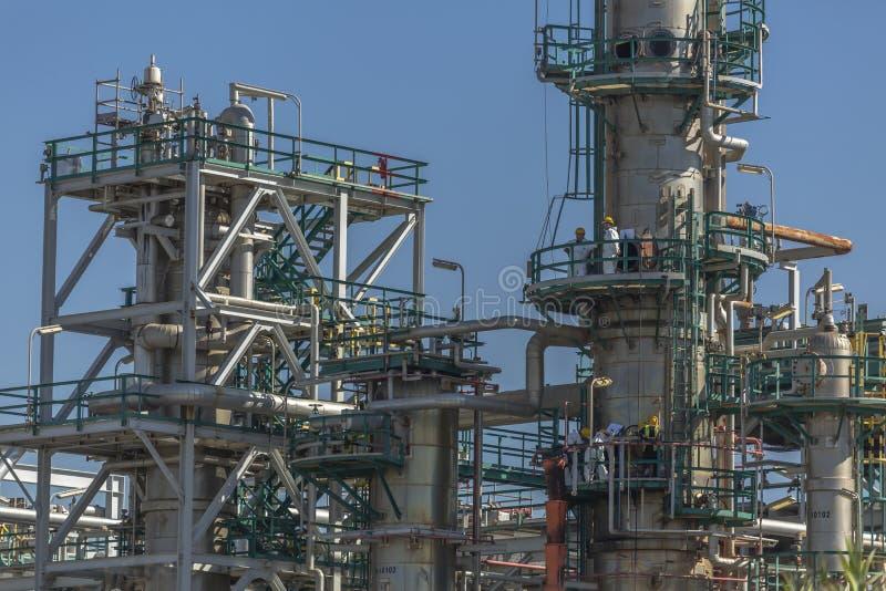 Visión en el complejo industrial de la refinería y de la gente de petróleo que trabajan adentro, con los edificios, el equipo y l imagenes de archivo