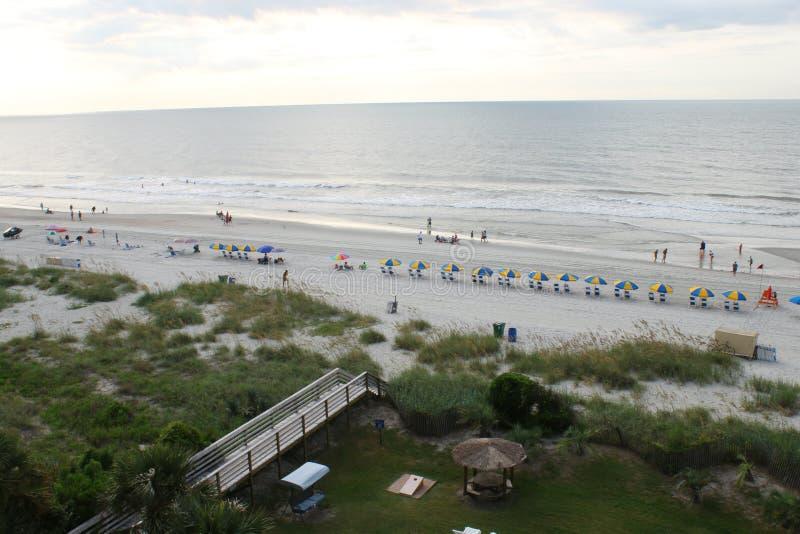 Visión en Myrtle Beach, los paraguas y las sillas esperando al persona que toma el sol foto de archivo libre de regalías