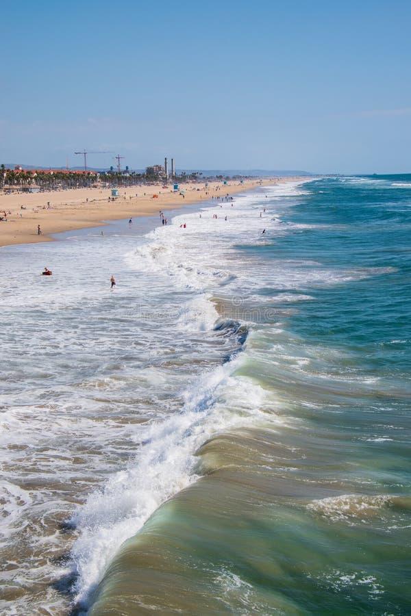 Visión encima del Huntington Beach con el océano áspero con los bañistas y las personas que practica surf opinión del abejón imagen de archivo