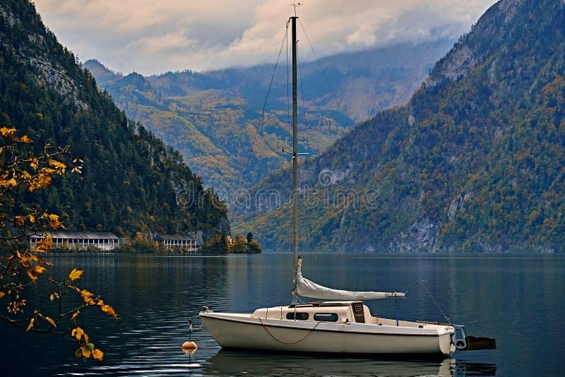Visión escénica hermosa sobre el lago austríaco tranquilo y pacífico de las montañas Barco o yate solo en la luz del sol de igual foto de archivo