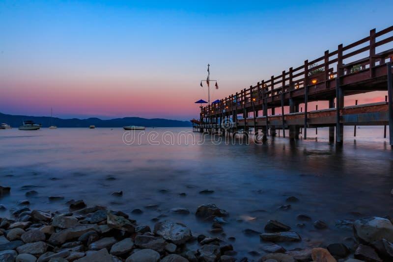 Visión escénica sobre el lago Tahoe en la puesta del sol por un embarcadero de madera viejo en la bahía de la cornalina, Califron imágenes de archivo libres de regalías