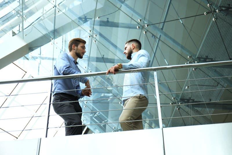 Visión inferior Dos hombres de negocios en ropa de sport que discuten en la oficina durante la reunión de negocios imagen de archivo