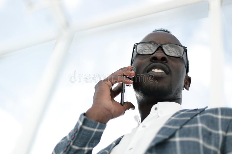Visión inferior Hombre de negocios sonriente que habla en un teléfono móvil fotos de archivo