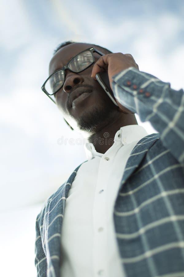Visión inferior un hombre de negocios serio que habla en un teléfono móvil imagenes de archivo