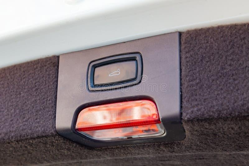 Visión interior con el botón eléctrico del ajuste del tronco con la lámpara de reflector roja y blanca del nuevo coche beige muy  foto de archivo libre de regalías