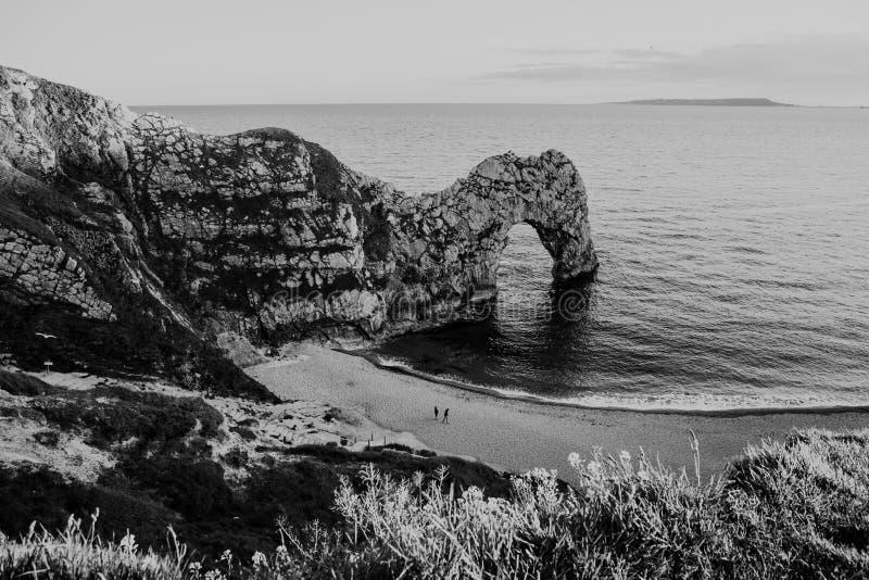 Visión negra y blanca desde la colina sobre la gente que camina en una playa por el mar y la puerta de Durdle, Dorset, Reino Unid foto de archivo libre de regalías