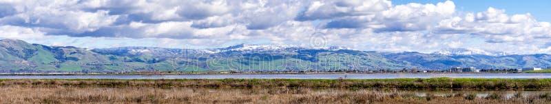 Visión panorámica hacia las colinas verdes y las montañas nevosas en un día de invierno frío llevado de las orillas de un pantano fotografía de archivo libre de regalías