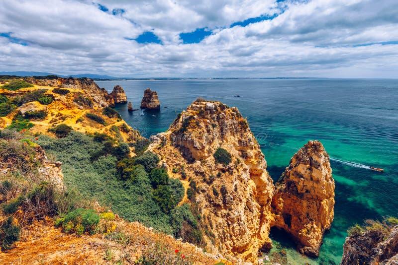 Visión panorámica, Ponta DA Piedade cerca de Lagos en Algarve, Portugal Rocas del acantilado y barco turístico en el mar en Ponta foto de archivo