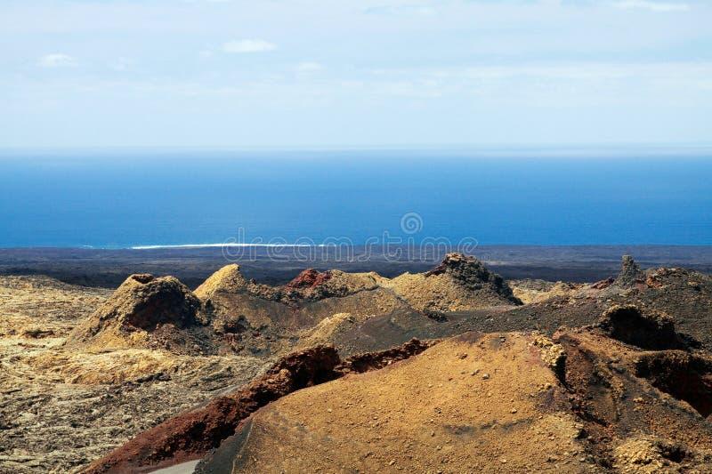 Visión panorámica sobre el campo de lava inútil en el horizonte borroso sin fin de Océano Atlántico en Timanfaya NP, Lanzarote, i imagen de archivo libre de regalías