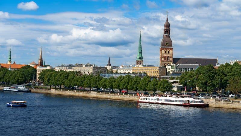 Visión panorámica a través del río del Daugava con el barco de cruceros y de la catedral de Riga en la ciudad vieja, Letonia, el  imagen de archivo libre de regalías