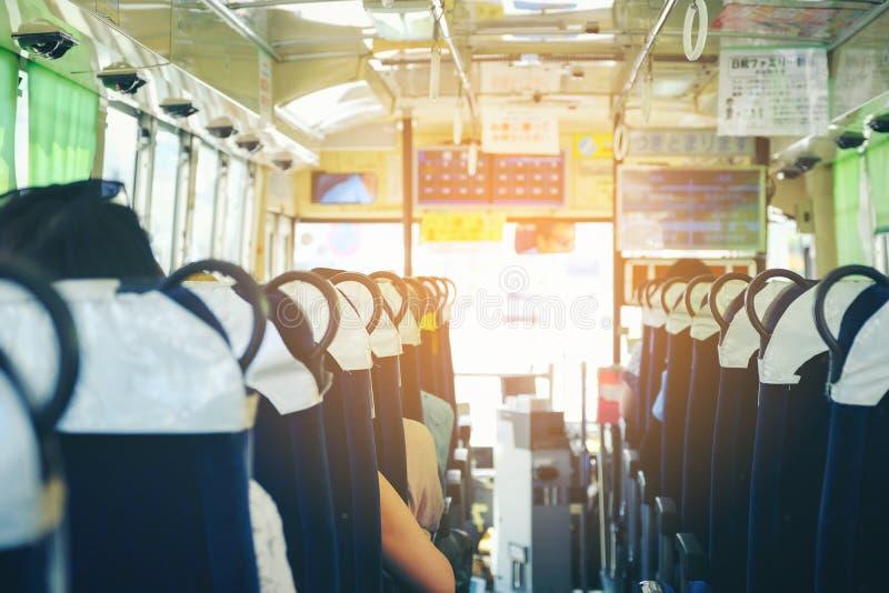 Visión por dentro del autobús con los pasajeros, autobús urbano de Naha con el PA imagen de archivo