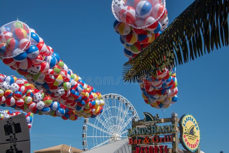 Visión que mira para arriba las pelotas de playa coloridas suspendidas en tubos de la malla sobre el paseo marítimo cerca de la b fotos de archivo