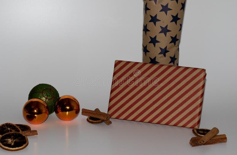 Visión sobre algunas bolas de la Navidad y decoración anaranjadas y verdes de la Navidad y con dos presentes y con un fondo blanc fotos de archivo