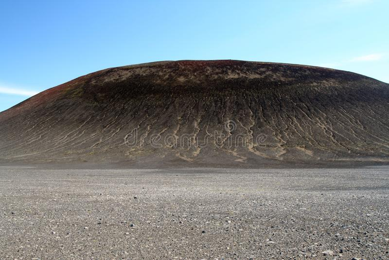 Visión sobre el llano estéril con nada que pequeñas piedras en la colina negra triste con los surcos que ponen en contraste con e fotografía de archivo libre de regalías