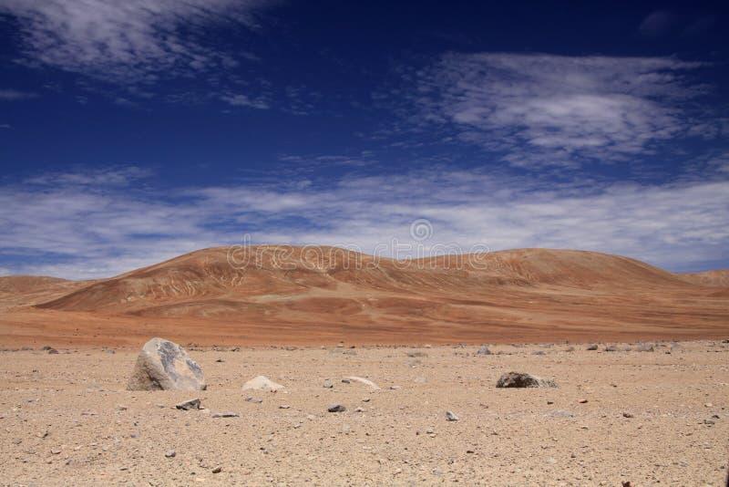 Visión sobre tierra estéril pedregosa en la formación roja de la colina que pone en contraste con el cielo azul y las nubes de ci fotografía de archivo