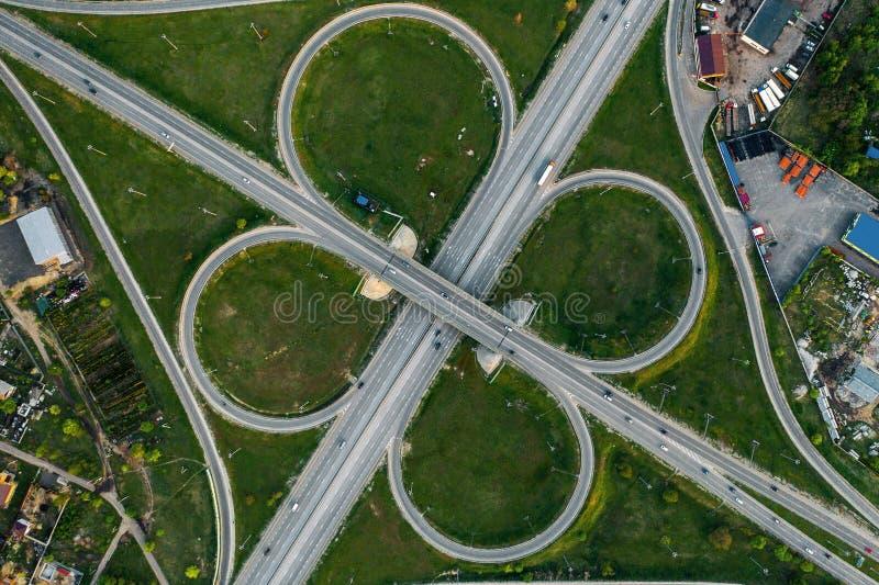 Visión superior aérea en la intersección de la carretera o empalme de camino con el tráfico del movimiento, de los coches y de ca fotografía de archivo