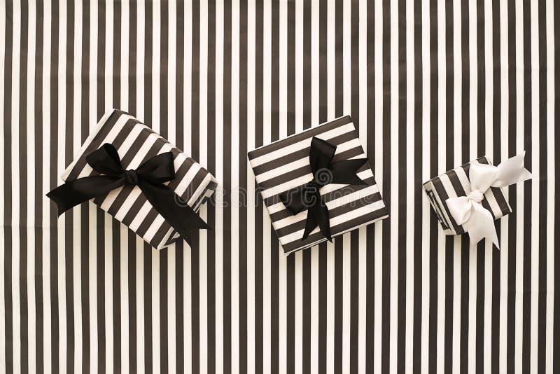 Visión superior Cajas de regalo blancos y negros en un fondo rayado imagenes de archivo