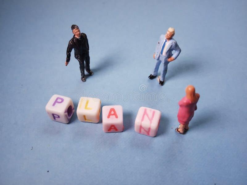 Visión superior cercana encima de la figura miniatura conceptual/del ejemplo hombre de negocios 2 y de 1 empresaria Discussing pa foto de archivo libre de regalías